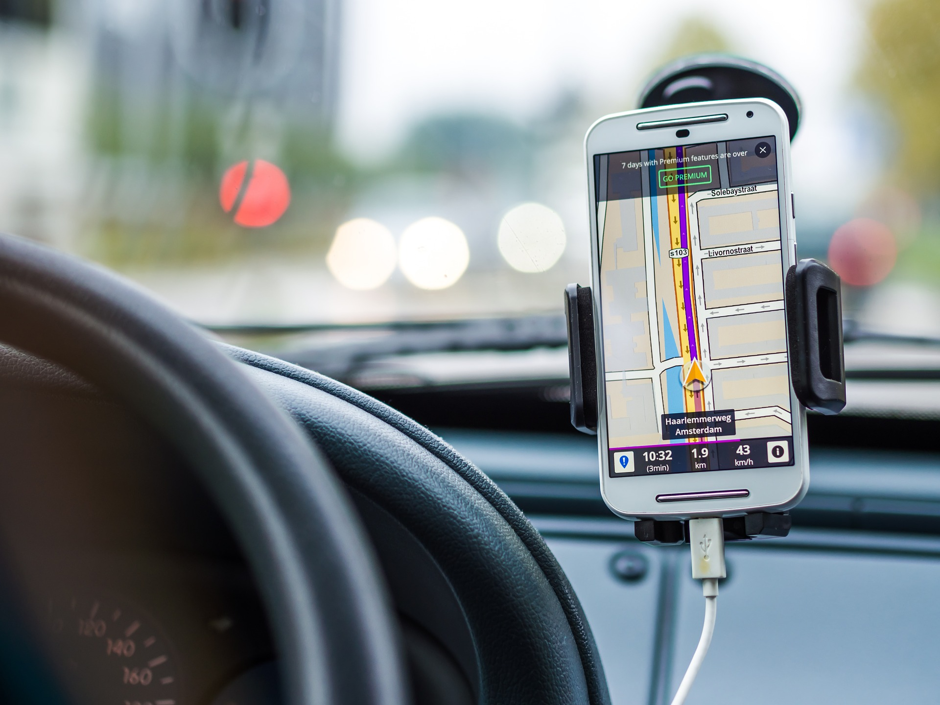 An image that shows a phone mounted sideways of car steering showing navigation
