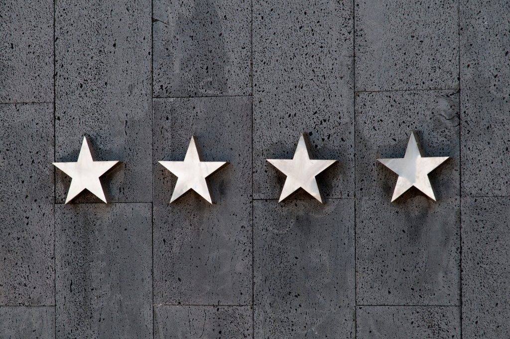 An image of grey background and four white stars on it to get positive hotel reviews