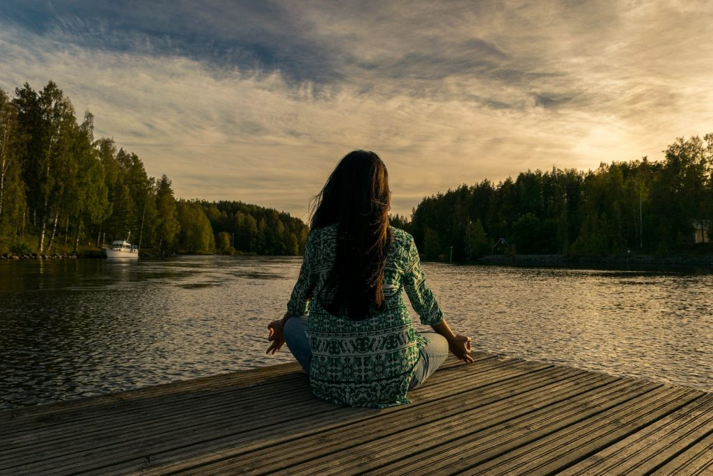 A women is sitting on the bay of river for health and wellness purpose